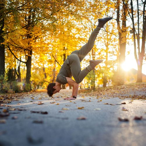 Side view of man doing handstand on road during autumn