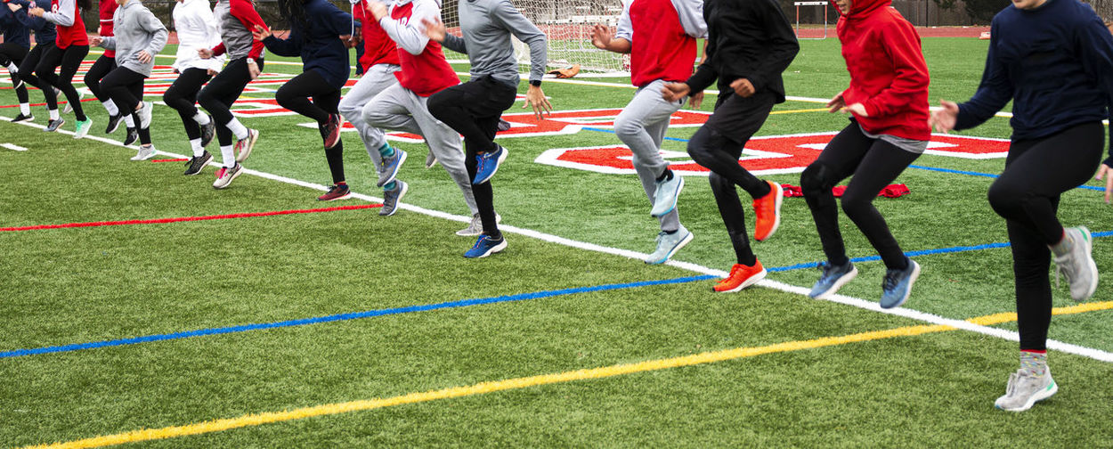 Low section of people running at soccer field