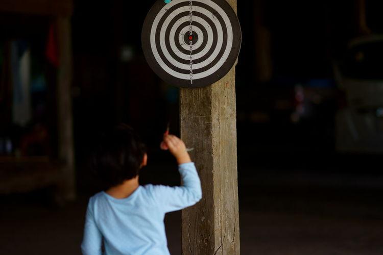 Rear view of boy throwing darts at dartboard at night