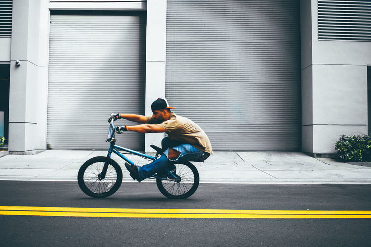 Man with bicycle on road in city