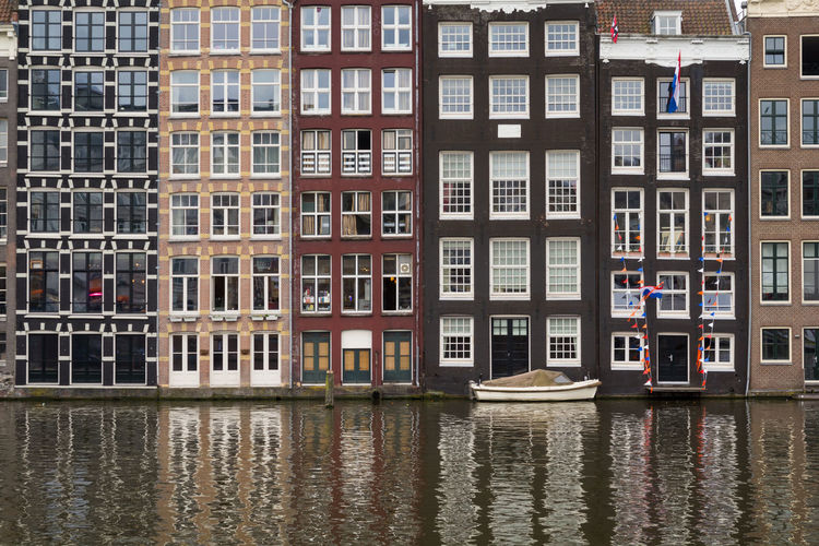 Facades of traditional colorful Dutch houses in Amsterdam, Holland Damrak Amstel Holland Façade Pattern Canal House Colorful Window Traditional Boat Waterfront Architecture Reflection Exterior Apartment City Cityscape Residential  Urban Water Travel Capital Real Estate Building