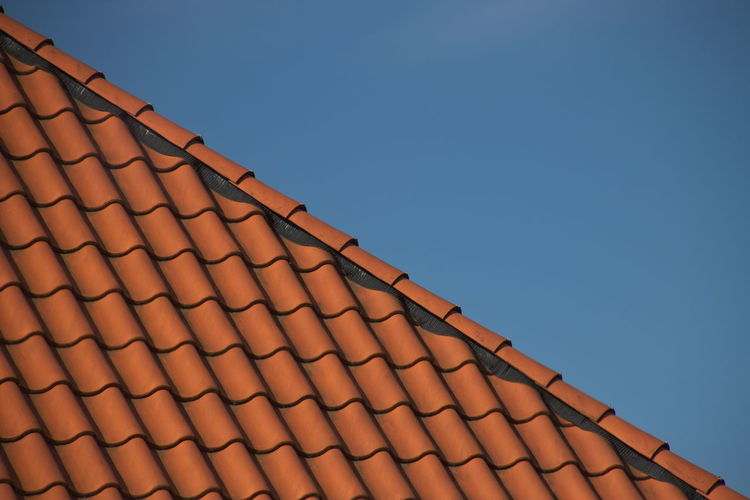 Low angle view of roof tiles against clear sky