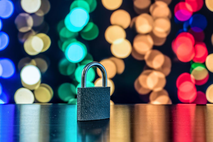 Close-up of padlock on table against colorful illuminated lights