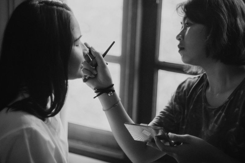Woman Applying Make-Up To Friend At Home