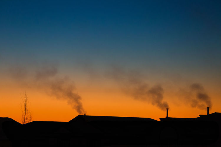 Smoke emitting from silhouette houses against clear sky during sunset