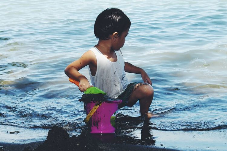Full length of boy playing in sea