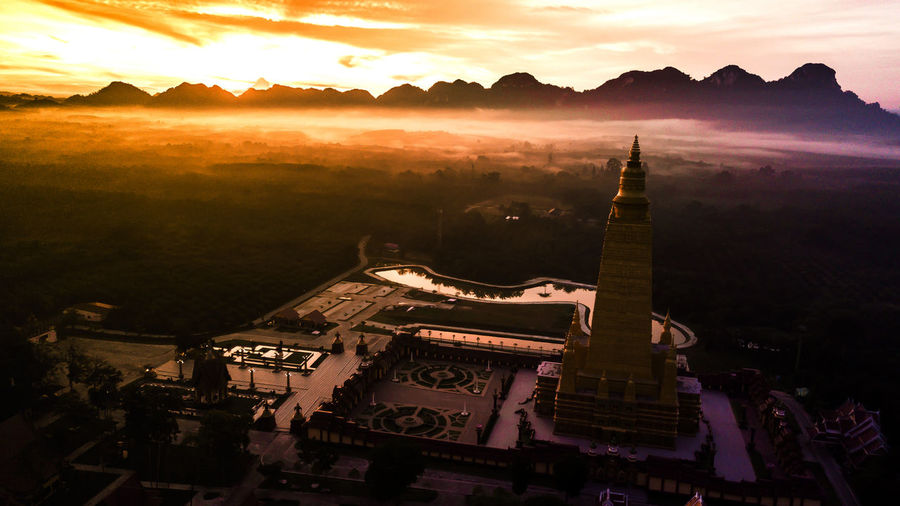 Aerial photo of Beautiful temples in the morning atmosphere , Thailand . ASIA Nature Background Agriculture Morning Drone  Architecture Temple Thailand View Asian  Building Art Buddhist Old Landmark Gold Aerial Landscape Buddha Clouds Culture Countryside Blue Buddhism Religion Beautiful Travel Rice Top Fields Sky Green Photo Tourism Trees Wat Built Structure Sunset Mountain Building Exterior Travel Destinations Belief Place Of Worship Cloud - Sky No People Spirituality High Angle View Orange Color City Scenics - Nature Outdoors Cityscape Spire