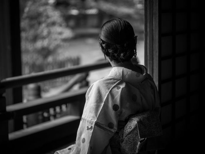 Rear view of woman in kimono standing in balcony