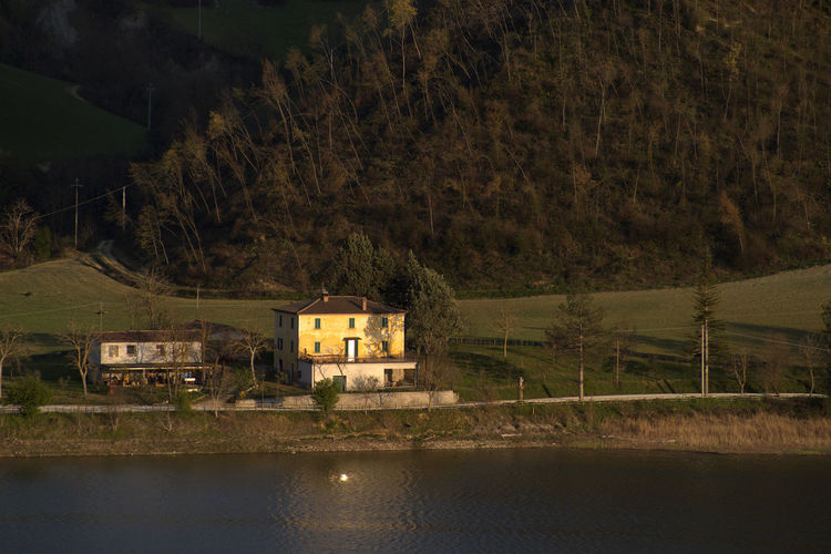 Aerial view of house by lake against trees