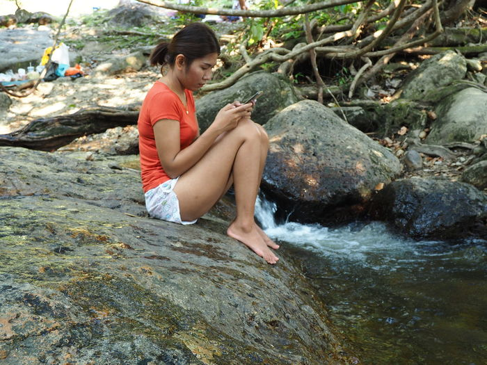 Side view of young woman sitting on rock