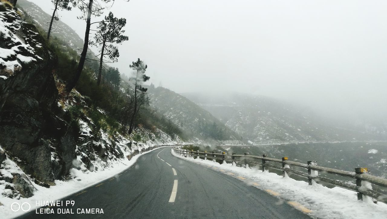 road, cold temperature, winter, transportation, snow, fog, direction, nature, the way forward, sky, mountain, sign, beauty in nature, tree, plant, scenics - nature, non-urban scene, day, no people, outdoors, snowing, diminishing perspective