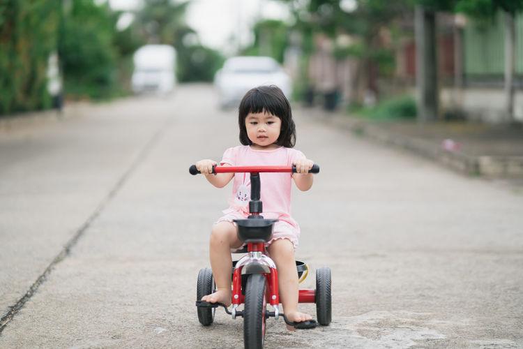 Portrait of cute boy riding toy car