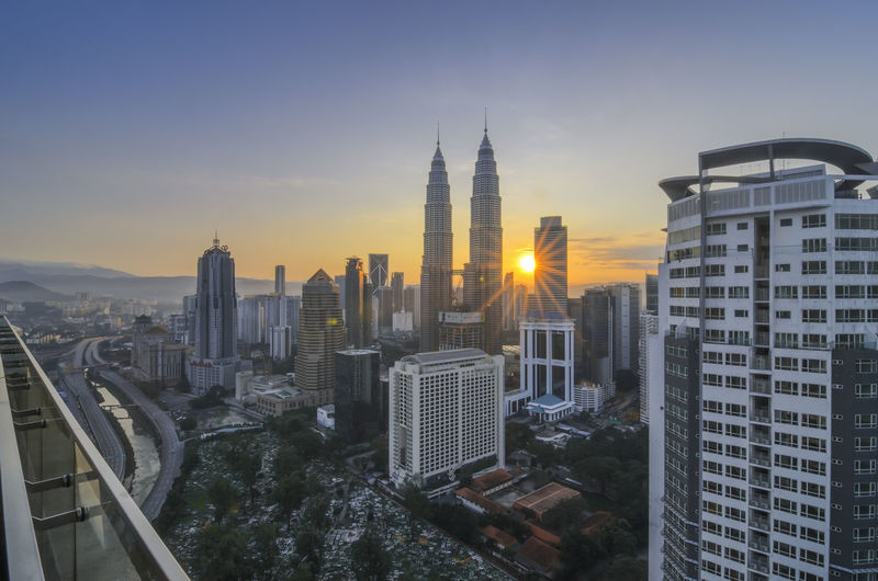 Petronas towers amidst buildings against sky during sunset