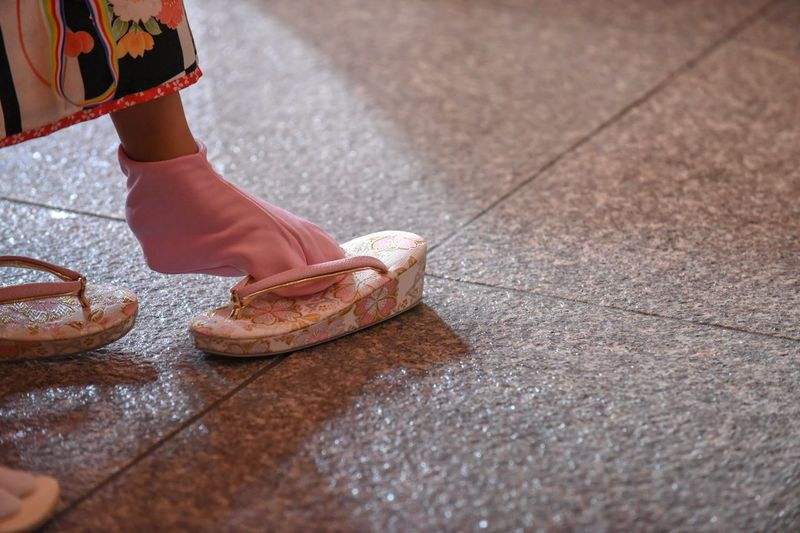 Low section of girl putting slippers while standing on floor