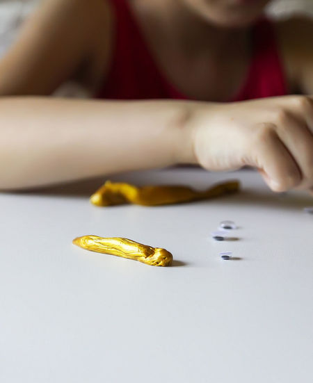 Midsection of girl playing with yellow clay on table
