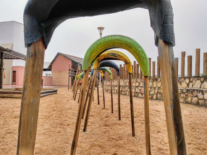 a tunnel on a playground made out of tyres and wood Playground Tunnel Gravel Tyres Yellow Rainy Winter Statue Sky Architecture Built Structure Sand Arch Building Exterior Archway