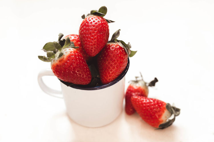 High angle view of strawberries on table against white background