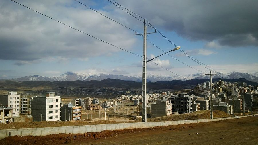 Rural-Urban Bird Telephone Line Mountain Electricity  Electricity Pylon Cable Flying Sky Mountain Range Cloud - Sky Power Cable Power Supply Residential Structure Electric Pole Residential District Residential Building TOWNSCAPE Human Settlement