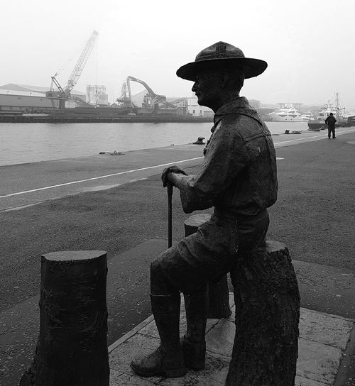 Statue of Robert Baden-Powell, founder of the Boy Scout movement, on Poole Quay, by sculptor David Annand; looking towards Brownsea Island, site of the first scout camp. Baden-Powell Monochrome Photography Poole Quay Scout Movement Boy Scouts Founder Statue Sculpture Misty Morning Sea And Sky Dorset, England 🌹 Samsung Galaxy S7 David Annand Centenary Sculpture