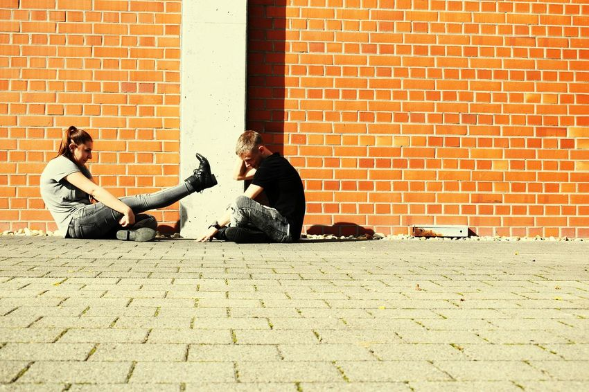 Urban kids Brick Wall Two People Sitting Togetherness Heterosexual Couple Relaxation Leisure Activity Friendship Couple - Relationship Lifestyles People Love Young Women Young Adult Urban Kids Urban Photography Urban Style