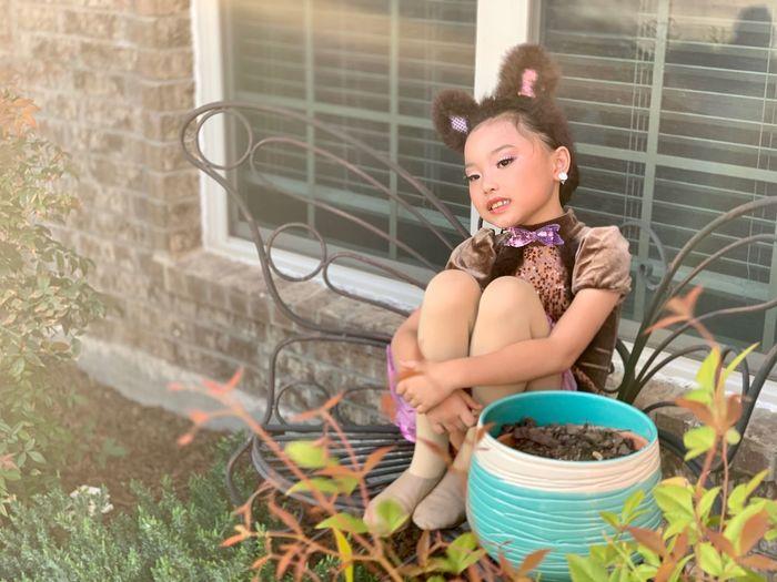 Woman looking away while sitting in yard