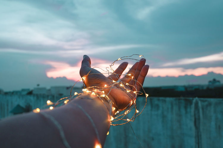 Cropped hand of person with illuminated string lights during sunset