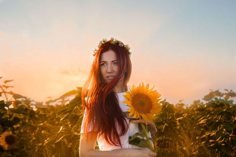 Woman holding sunflower against sky during sunset
