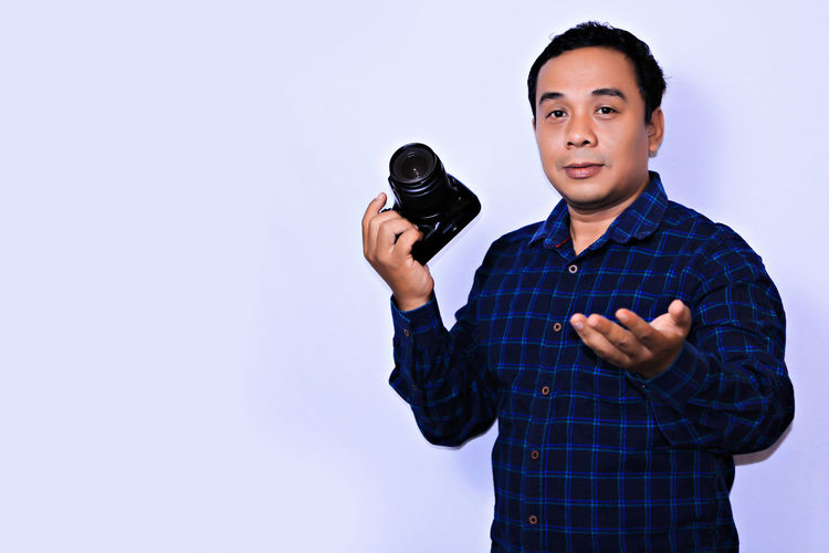 Portrait young Asian Photographer Studio Shot One Person Waist Up Indoors  Portrait Front View Young Adult White Background Holding Standing Adult Copy Space Looking At Camera Men Cut Out Checked Pattern Casual Clothing Expertise Males