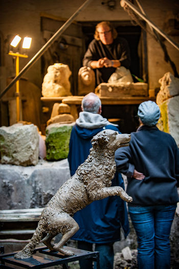 Art Market Artificial Light Day Dog Sculpture Expert Discussion Indoors  Occupation Outdoors People Sculptor Sculpture Statue Working