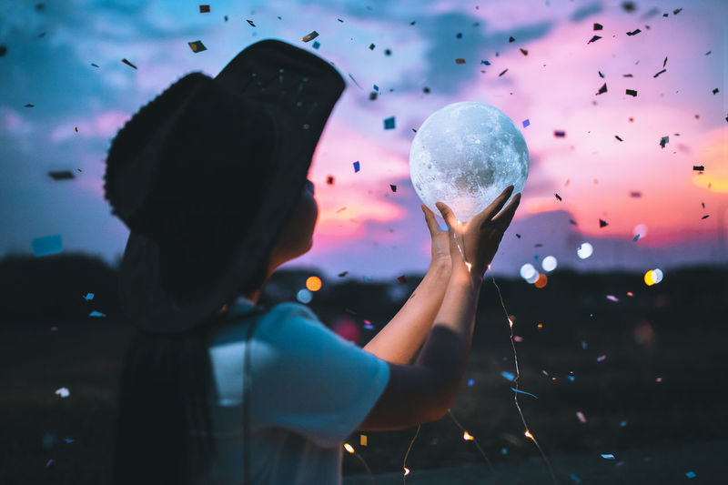 Girl Holding Crystal Ball Against Sky During Sunset