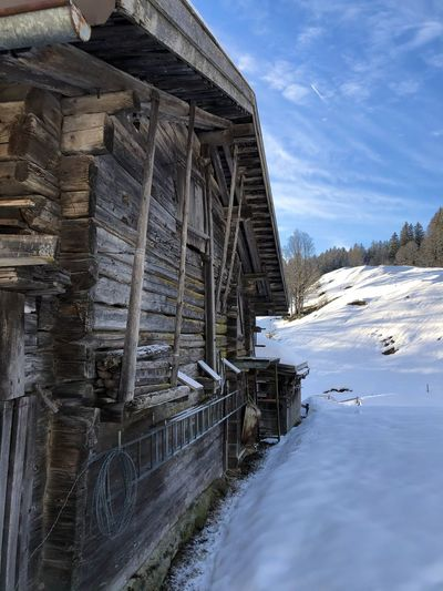 Built structure by frozen river against sky during winter