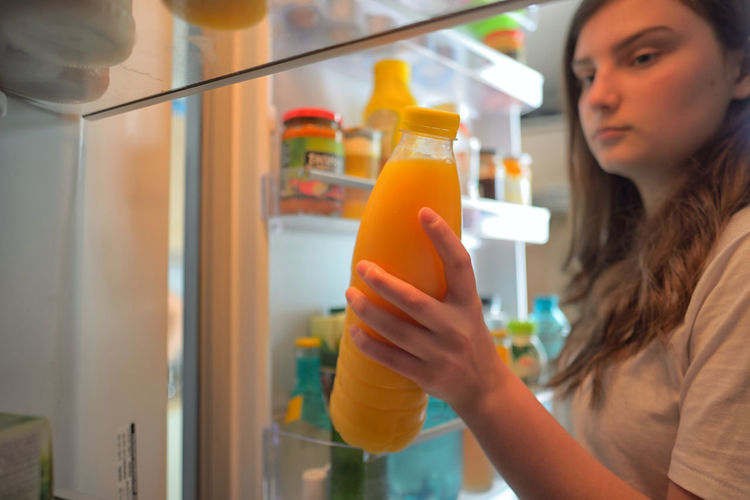 Teenage girl removing juice bottle from refrigerator