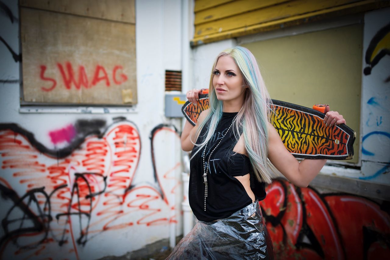 graffiti, young adult, young women, one person, front view, real people, fashion, beautiful woman, portrait, lifestyles, built structure, leisure activity, building exterior, standing, outdoors, dyed hair, architecture, day, fashion model, blond hair