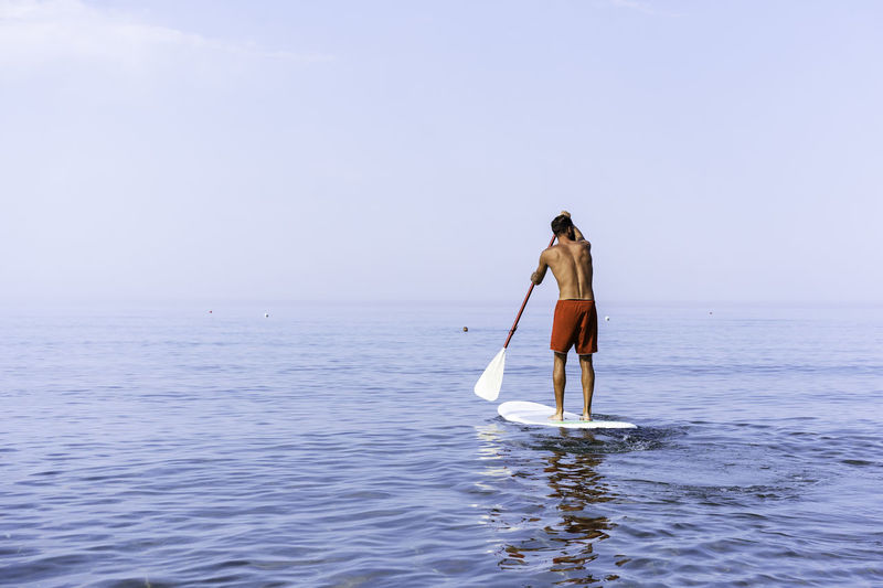 Rear view of shirtless man standing on paddleboard in sea