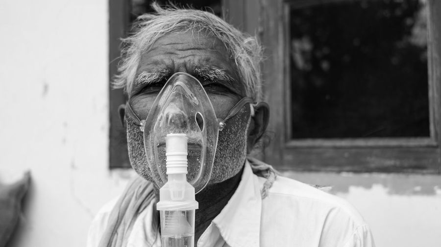 Elder person infected with covid 19 disease. patient inhaling oxygen wearing mask with liquid oxygen