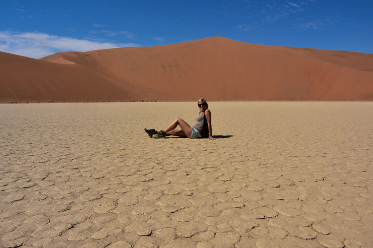 Man sitting on sand dune in desert