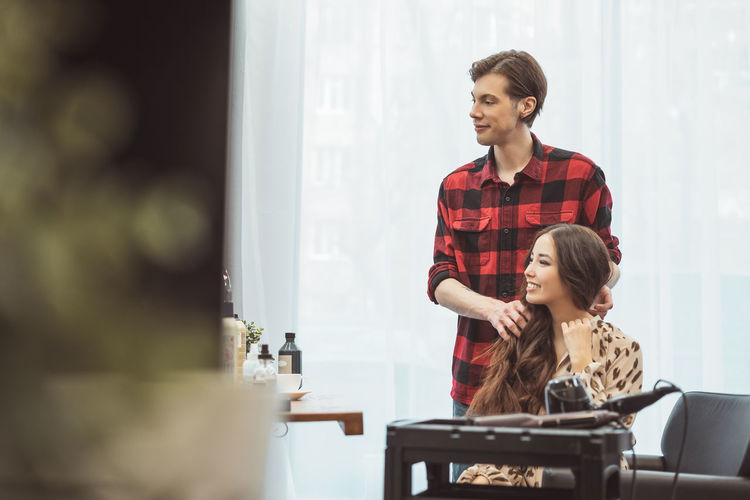 Stylist barber styling long hair for beautiful asian young woman in beauty salon, working moment