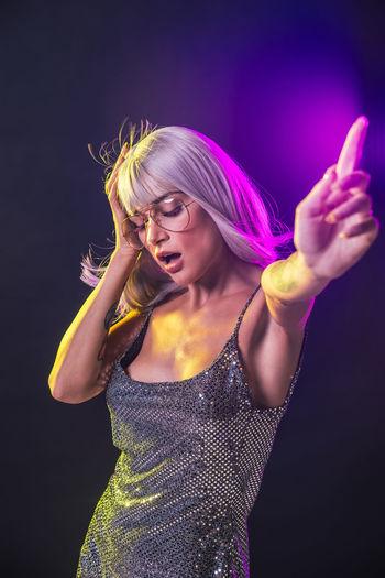 Beautiful woman dancing against black background