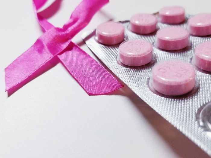 Close-up of blister pack and pink ribbon over white background