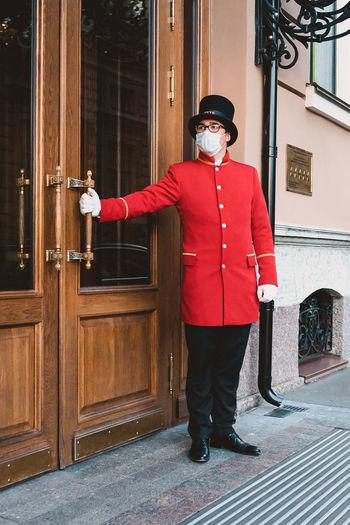 Full length portrait of man standing by door