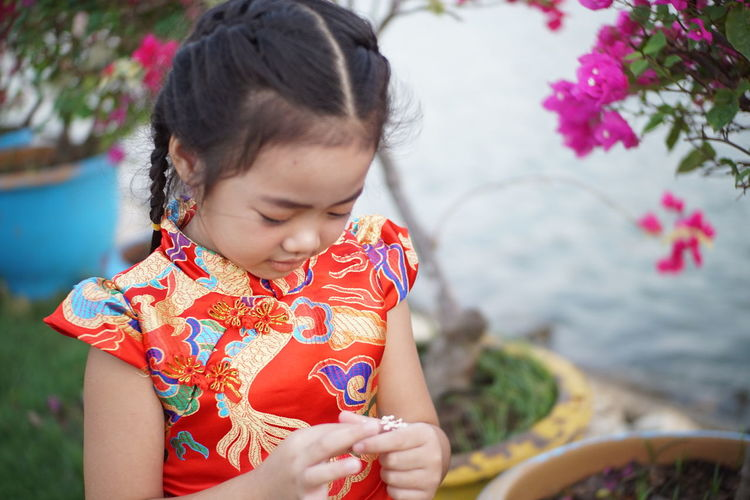 Close-up of cute girl holding flower by plants