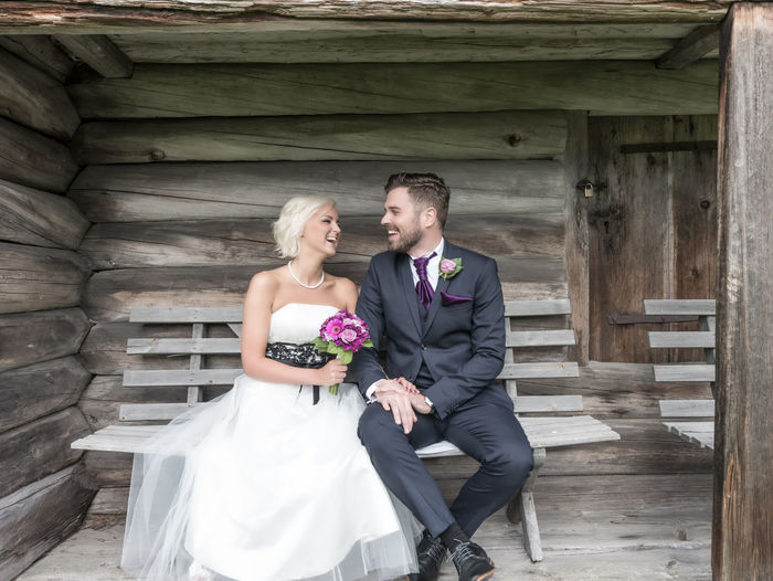 Happy Bride And Groom Sitting On Bench Against Wooden Wall