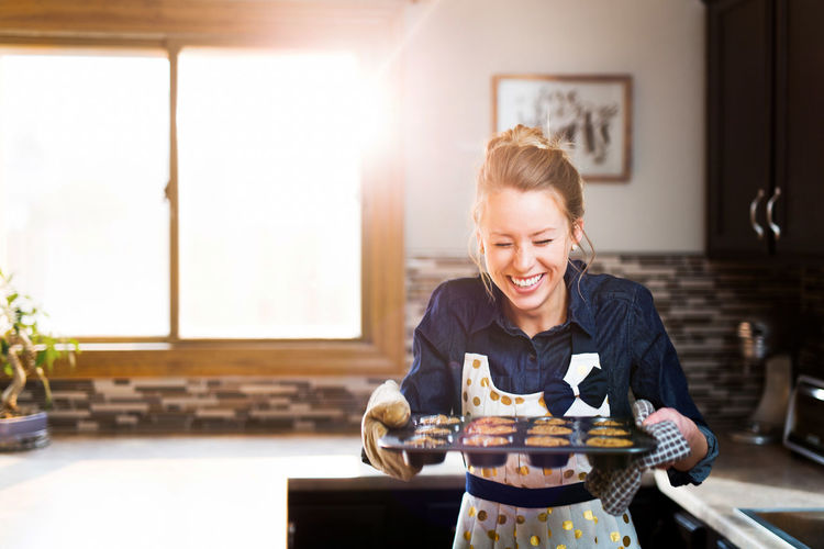 Cooking Freshness Laughing Adult Adults Only Baking Cheerful Domestic Life Enjoyment Food Food And Drink Front View Happiness Holding Indoors  Muffins <3 One Person One Woman Only One Young Woman Only Only Women People Preparation  Smiling Young Adult Young Women