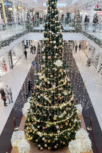 Huge decorated Christmas Tree, from above, in a shopping mall wirh people walking... christmas tree Christmas Decoration Tree High Angle View Christmas Close-up Bauble Celebration Event Christmas Ornament Christmas Lights Decorating The Christmas Tree Fairy Lights Christmas Bauble