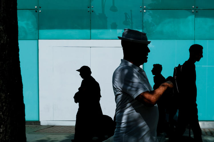 Group of people in shadows walking past blue wall