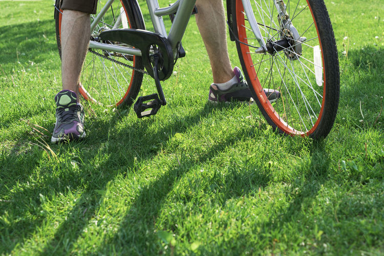 Low section of man riding bicycle on grass