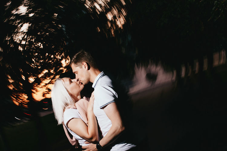 Couple kissing while standing trees at dusk