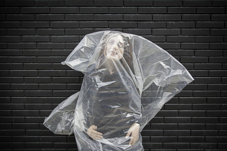 Portrait Of Mid Adult Woman In Plastic Bag Standing Against Brick Wall