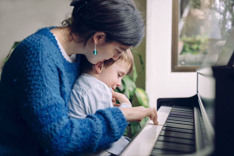 Mother and son playing piano at home