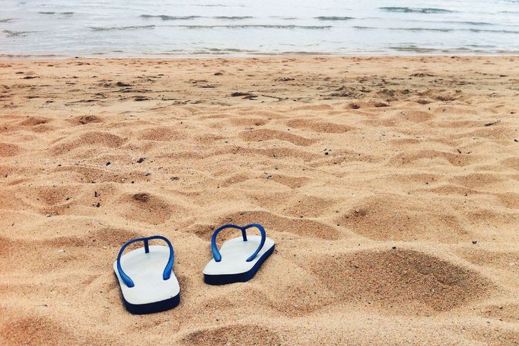 Pair of slippers on sand at beach